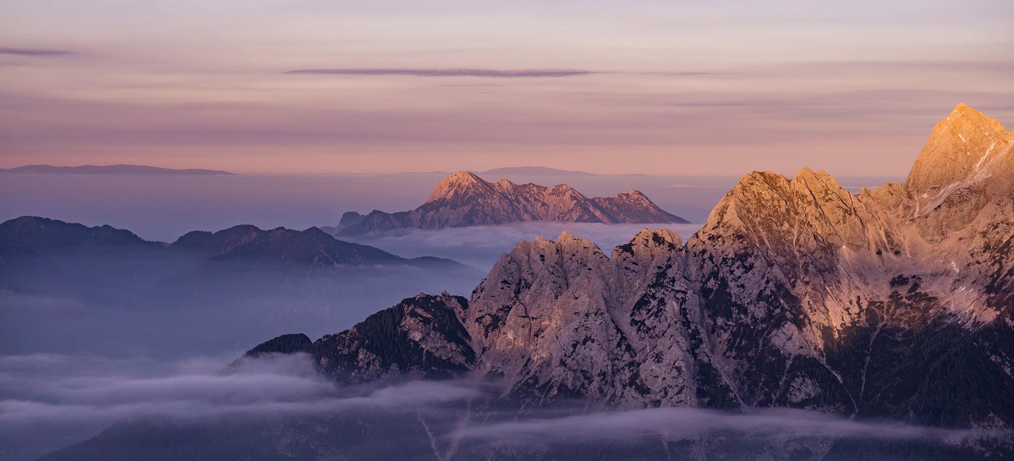 Die nebelverhangenen Julischen Alpen im Sonnenuntergang