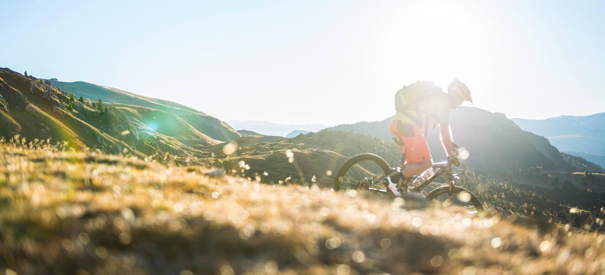 Mountainbiker fährt bei Sonnenschein durch die Berge