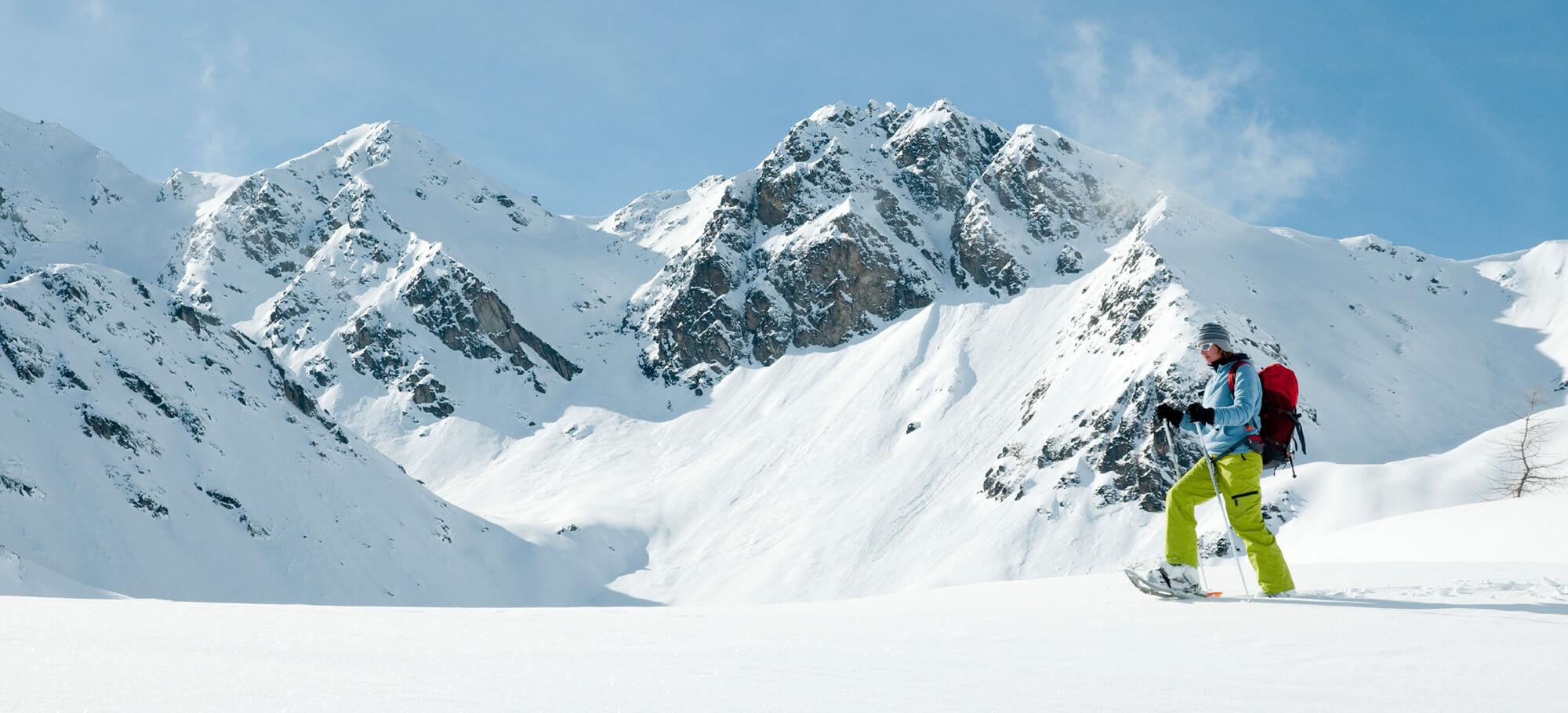 Frau bei einer Schneeschuhwanderung durch das verschneite Gebirge