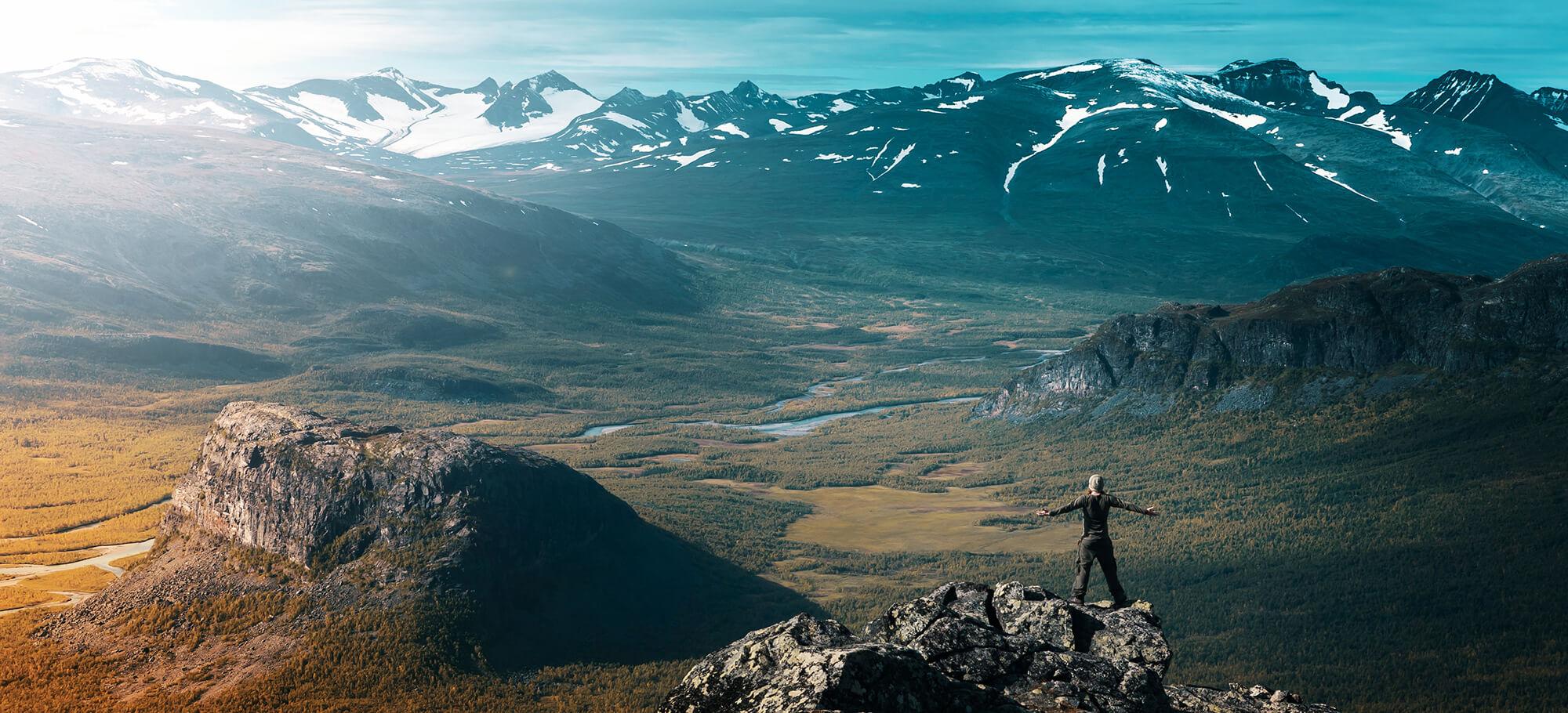 Glücklicher Wanderer genießt auf dem Gipfel das Bergpanorama