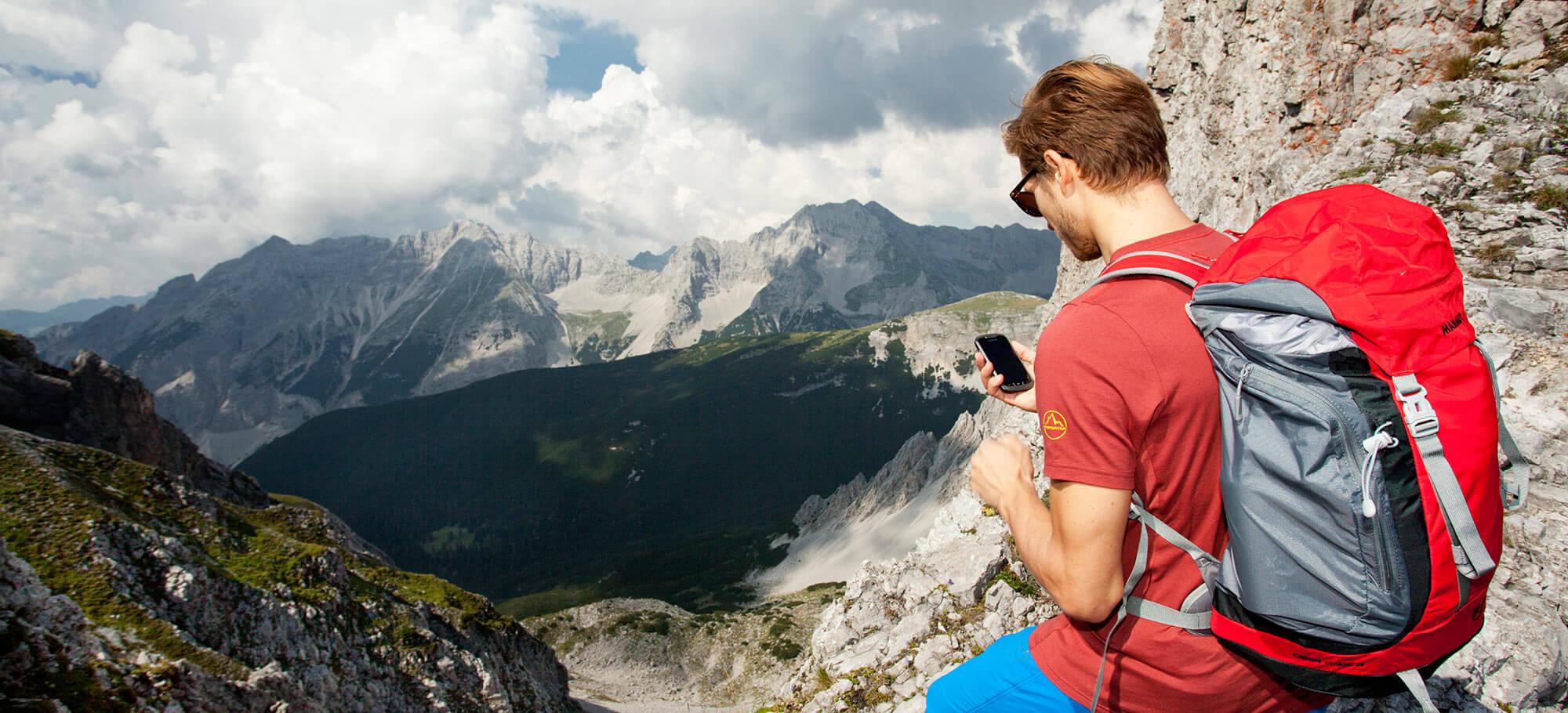 Mann mit Smartphone in den Bergen