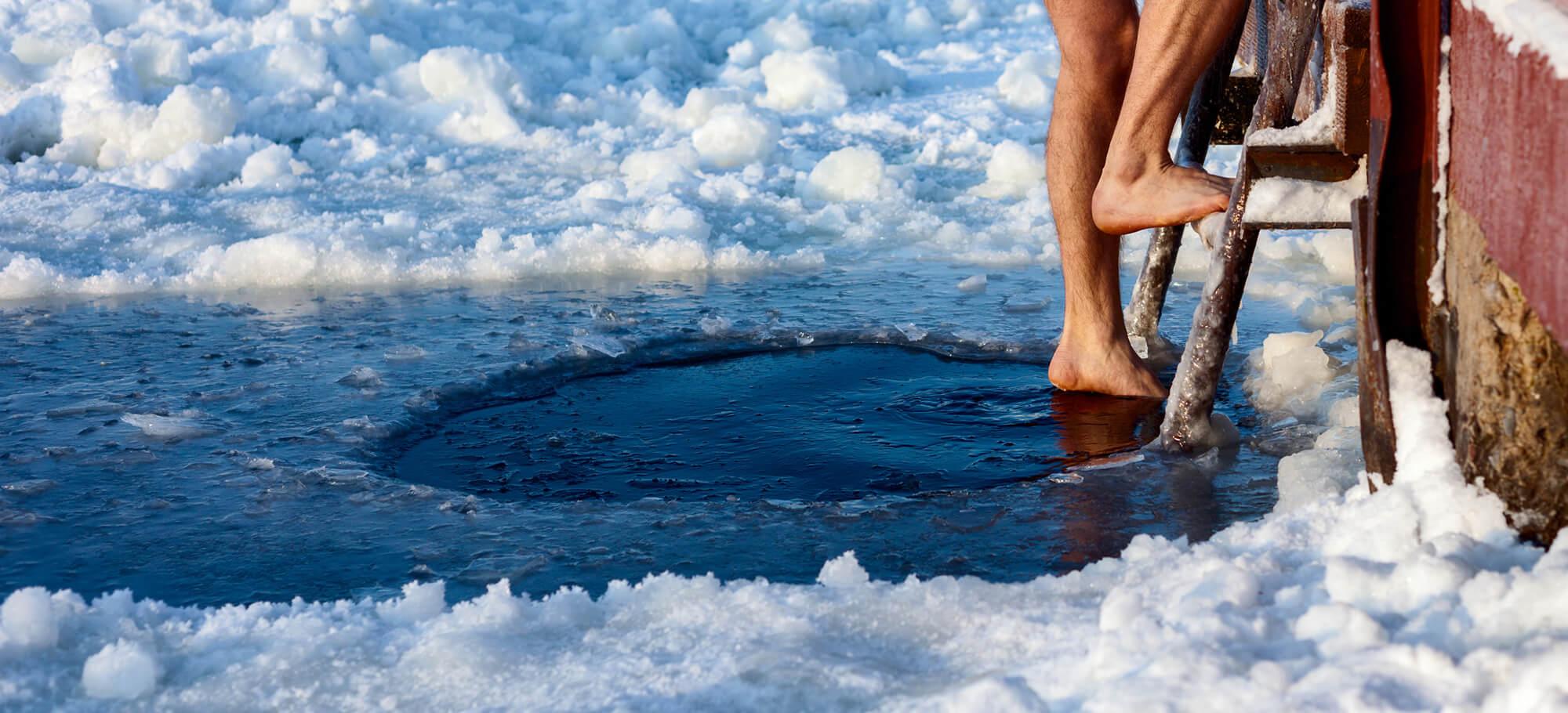 Mann steigt beim Eisbaden in zugefrorenen See