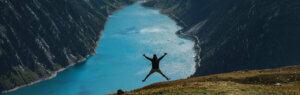 Mann auf Berg springt in die Luft, im Hintergrund See