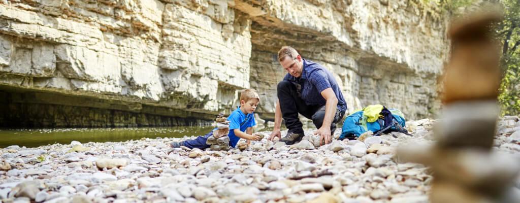 Vater mit Sohn spielt in Wutachschlucht mit Steinen