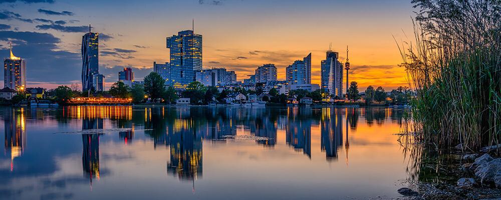 Blick von der Donau aus auf Wien am Abend
